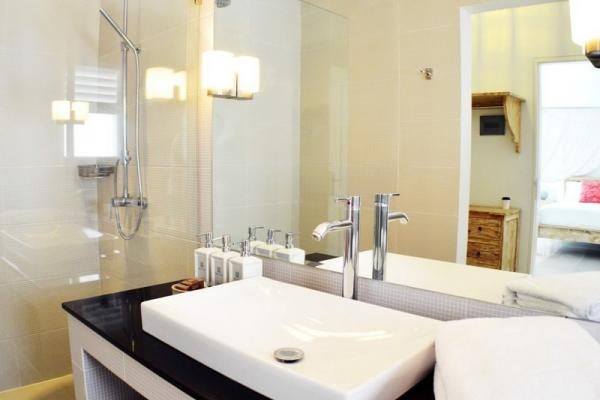 Indoor Shower And Single Sink With Bathroom Amenities And Towel